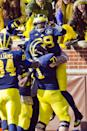 Michigan quarterback Devin Gardner (98) is lifted by offensive lineman Ben Braden (71) celebrating a touchdown in the first quarter of an NCAA college football game against Ohio State in Ann Arbor, Mich., Saturday, Nov. 30, 2013. (AP Photo/Tony Ding)