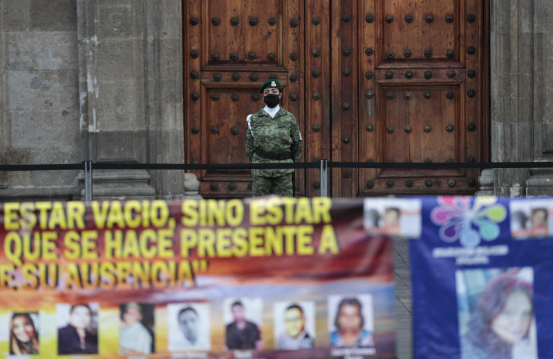A soldier wearing a mask amid the new coronavirus pandemic watches a protest by relatives of the disappeared in front of the National Palace in Mexico City, Thursday, June 4, 2020. Relatives of different groups searching for the disappeared protested the cut to the budget destined for their search. (AP Photo/Eduardo Verdugo)