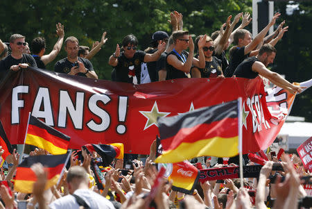Germany's coach Loew and members of Germany's 2014 Brazil World Cup squad applaud fans during celebrations at 'fan mile' in Berlin