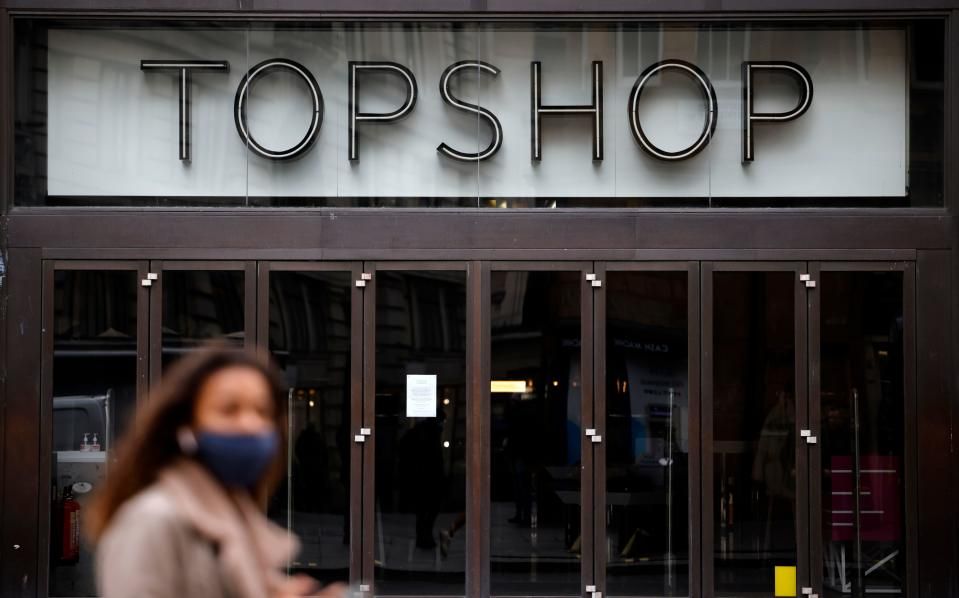 "A pedestrian wearing a face covering due to the COVID-19 pandemic, walks past a closed-down Topshop clothes store, operated by Arcadia, on Oxford Street in central London on November 27, 2020. - British fashion empire Arcadia, which owns Topshop stores, announced Friday it was evaluating several ""rescue options"" to save its brands after media reports suggested an imminent bankruptcy attributed to the coronavirus pandemic. Bankruptcy of the group, which has 15,000 employees and more than 500 stores, would be a thunderclap in British commerce, already hit hard by the health crisis and the rise in online shopping. (Photo by Tolga Akmen / AFP) (Photo by TOLGA AKMEN/AFP via Getty Images)"