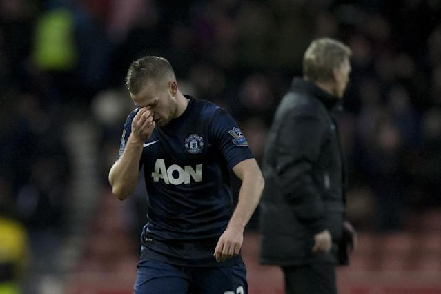 Manchester United's Tom Cleverley holds his nose after his team's 2-1 loss at Stoke in their English Premier League soccer match at the Britannia Stadium, Stoke, England, Saturday Feb. 1, 2014. (AP Photo/Jon Super)