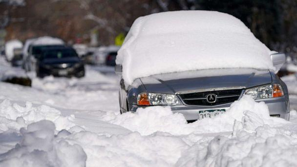 PHOTO: A sedan is buried after more than a foot of snow left by a late winter storm that swept over the region on Feb. 25, 2021, in Denver, Colorado. (David Zalubowski/AP)