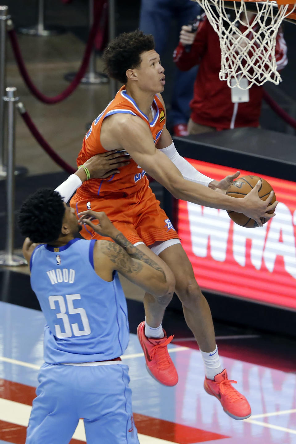 Oklahoma City Thunder center Isaiah Roby, right, puts up a shot past Houston Rockets center Christian Wood (35) during the second half of an NBA basketball game Sunday, March 21, 2021, in Houston. (AP Photo/Michael Wyke)