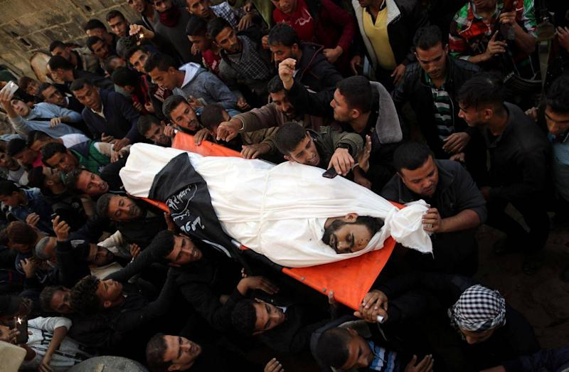 Mourners carry the body of Palestinian Khaled Qwaider, who was killed in an Israeli air strike, during his funeral, in Khan Younis in the southern Gaza Strip (REUTERS/Suhaib Salem)