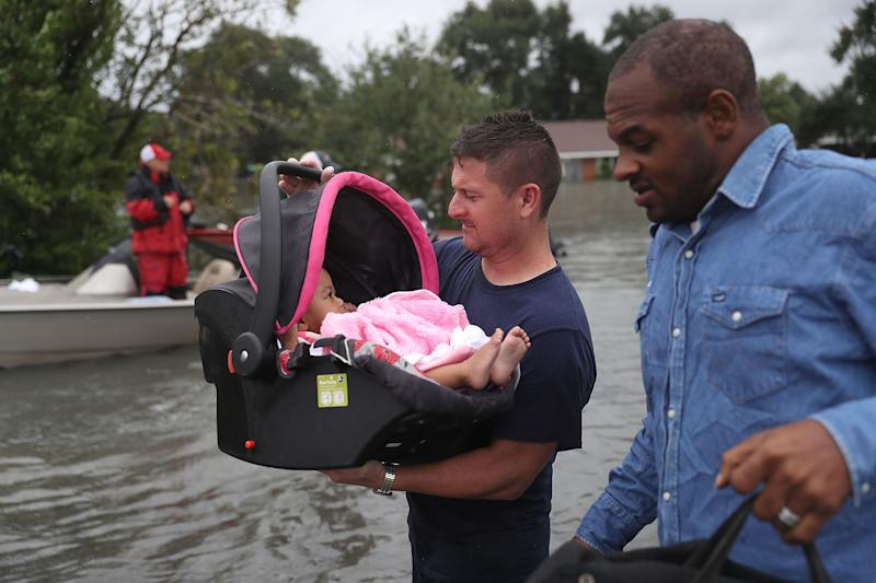 A rescue worker carries a baby to dry land in Port Arthur, Texas, on Aug. 30, 2017. (Joe Raedle via Getty Images)