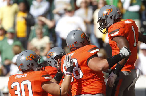 Oklahoma State running back Joseph Randle, right, celebrates with teammates following a touchdown against Baylor in the first quarter of an NCAA college football game in Stillwater, Okla., Saturday, Oct. 29, 2011. Randle set career-highs by running for 152 yards and four touchdowns as Oklahoma State won 59-24. (AP Photo/Sue Ogrocki)