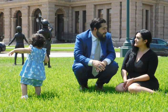 Donovon Rodriguez, chief of staff for Texas state Rep. Ray Lopez, walks around the Texas capitol with his wife, Jenny Tavarez, and daughter, Evelyn Belle Rodriguez, for whom he is the sole provider, Monday, July 26, 2021 in Austin, Texas. Rodriguez could lose his job by Sept. 1, if legislative budget funding is not restored. Texas. (AP Photo/Acacia Coronado)