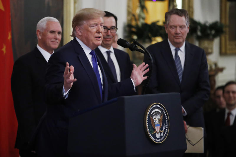 "President Donald Trump, gestures, as Vice President Mike Pence, back left, Secretary of Treasury, Steven Mnuchin, back center, and U.S. Trade Representative Robert Lighthizer, right, listen during a signing ceremony of the ""phase one"" of a US China trade agreement, in the East Room of the White House, Wednesday, Jan. 15, 2020, in Washington. (AP Photo/Steve Helber)"