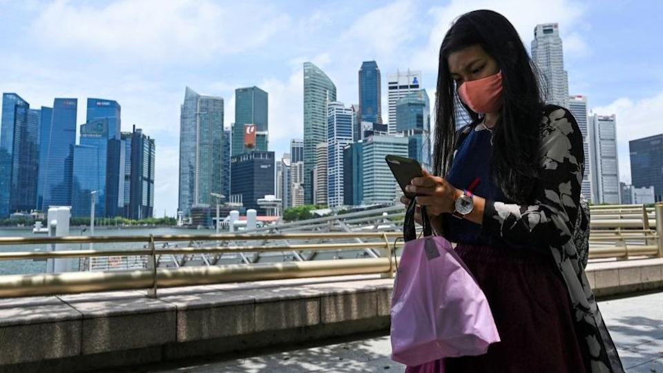 A woman absorbed by her mobile phone in front of the Singapore skyline
