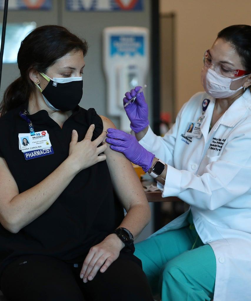 MIRAMAR, FLORIDA – DECEMBER 14: Diana Carolina, a pharmacist at Memorial Healthcare System, receives a Pfizer-BioNtech Covid-19 vaccine from Monica Puga, ARNP at Memorial Healthcare System, on December 14, 2020 in Miramar, Florida. The hospital system announced it will be vaccinating their frontline workers that are in contact with COVID-19 patients. (Photo by Joe Raedle/Getty Images)