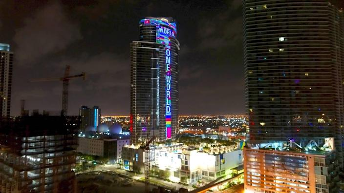 """The 60-story Paramount Miami Worldcenter at 851 NE First Ave in Downtown Miami, will light up every night with hundreds of fluttering flags and the words """"One World, One Prayer,"""" until all of the missing people in Surfside's building collapse are found. Pictured above is a May 19, 2020 photo when the skyscraper was lit up during the week of the 39th annual funeral observance of music legend Bob Marley. (Bryan Glazer/World Satellite Television News via AP Images)"""