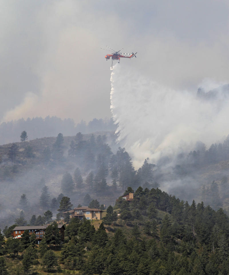 A helicopter drops water on trees burning behind homes on the High Park wildfire near Fort Collins, Colo., on Monday, June 11, 2012. The wildfire is burning out of control in northern Colorado, while an unchecked blaze choked a small community in southern New Mexico as authorities in both regions battled fires Monday.  (AP Photo/Ed Andrieski)