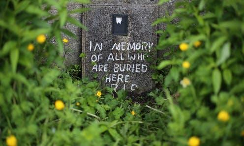 """<span class=""""caption"""">A makeshift memorial to the children buried at the Tuam mother and baby home, whose identification in 2013 led to the mother and baby homes inquiry.</span> <span class=""""attribution""""><span class=""""source"""">Niall Carson/PA</span></span>"""