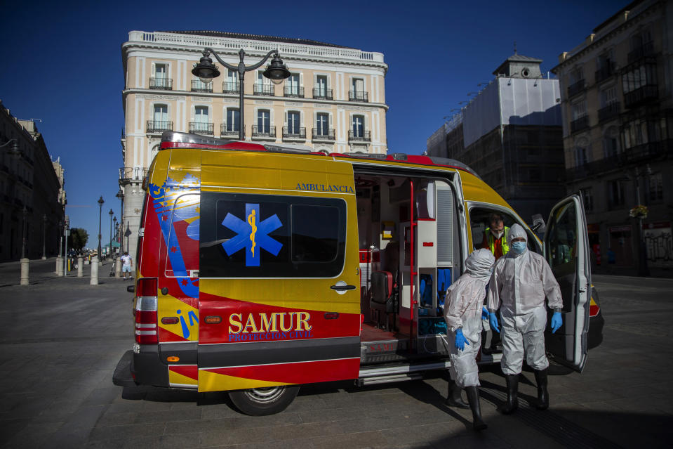 Health workers in personal protection equipments arrive at the Puerta del Sol in Madrid, Spain, Friday, Aug. 28, 2020. Spanish authorities have announced new restrictions to prevent COVID-19. (AP Photo/Andrea Comas)