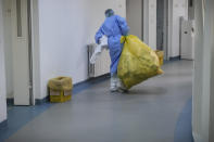 A woman carries a sack of medical waste at the COVID-19 unit of the Marius Nasta National Pneumology Institute in Bucharest, Romania, Thursday, Sept. 23, 2021. Daily new coronavirus infections in Romania, a country of 19 million, have grown exponentially over the last month, while vaccine uptake has declined to worrying lows. Government data shows that 91.5% of COVID-19 deaths in Romania between Sept. 18-23 were people who had not been vaccinated. (AP Photo/Vadim Ghirda)