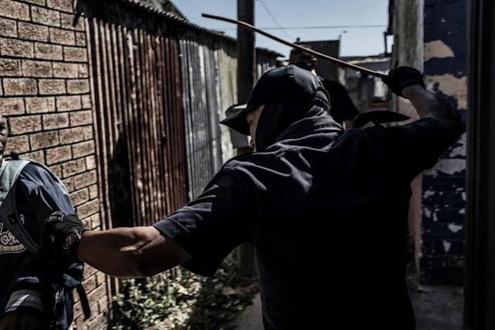 Lockdown enforcement: A policeman in the Cape Flats area of Cape Town forces a loitering man to go home (AFP Photo/PIETER BAUERMEISTER)