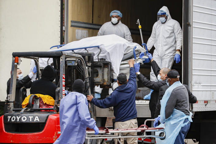 A plastic-wrapped body is unloaded from a refrigerated truck and handled by medical workers at the Brooklyn Hospital Center in New York. (John Minchillo / AP)