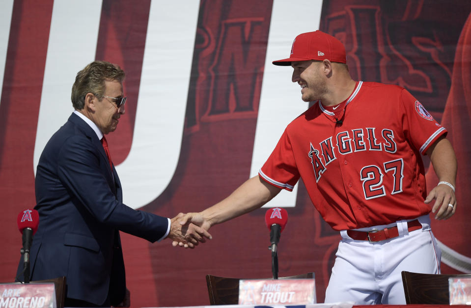 Los Angeles Angels owner Arte Moreno, left, shakes hands with center fielder Mike Trout during a news conference to talk about Trout's 12-year, $426.5 million contract, prior to the team's exhibition baseball game against the Los Angeles Dodgers Sunday, March 24, 2019, in Anaheim, Calif. (AP Photo/Mark J. Terrill)
