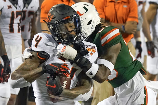 Oklahoma State wide receiver Tay Martin (4) makes a reception in front of Miami cornerback Te'Cory Couch during the first half of the Cheez-it Bowl NCAA college football game, Tuesday, Dec. 29, 2020, in Orlando, Fla. (AP Photo/John Raoux)