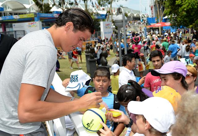 MELBOURNE, AUSTRALIA - JANUARY 16: Milos Raonic of Canada signs autographs for fans during day three of the 2013 Australian Open at Melbourne Park on January 16, 2013 in Melbourne, Australia. (Photo by Vince Caligiuri/Getty Images)