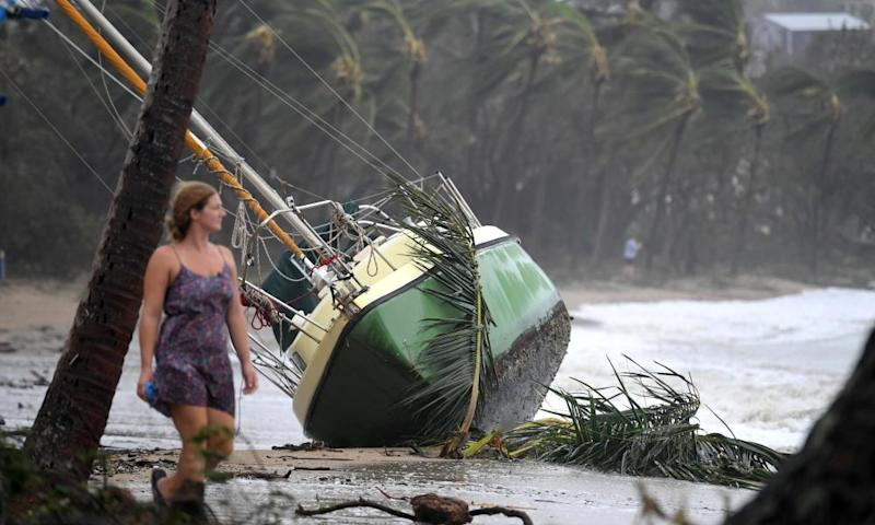 A local resident walks past a yacht that was washed ashore after Cyclone Debbie hit the northern Queensland town of Airlie Beach in March 2017.