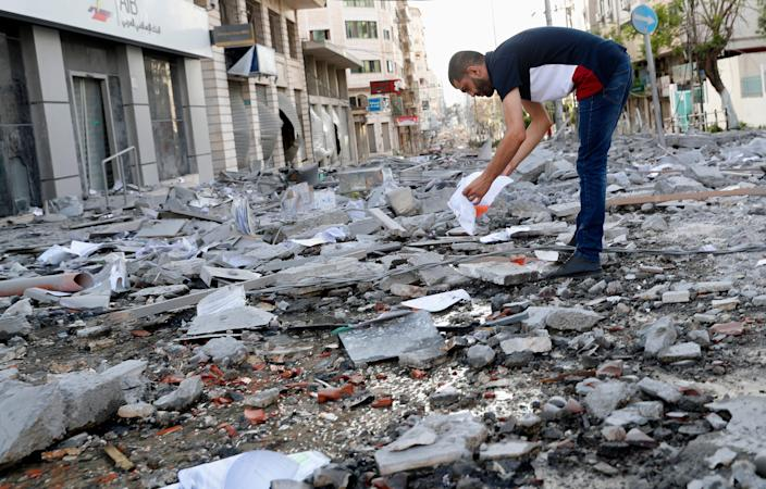 A man inspects the rubble of destroyed commercial building and health care clinic after an Israeli airstrike in Gaza City on May 17, 2021.