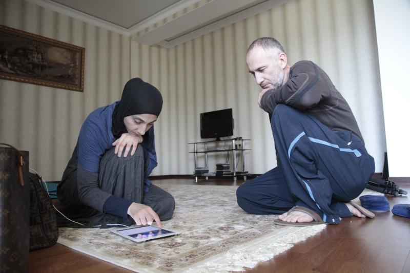 Zubeidat Tsarnaeva, left, and husband Anzor Tsarnaev show videos on an iPad they say show their sons could not have been involved in last month's Boston Marathon bombings in their new apartment in Makhachkala, regional capital of Dagestan, Russia, Friday, May 30, 2013. Authorities accuse Tamerlan Tsarnaev, who was slain in a shootout with police, and his younger brother Dzhokhar of organizing the attacks, which killed three. (AP Photo/Musa Sadulayev)