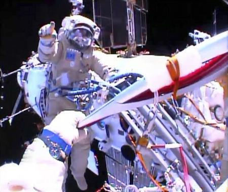 Russian astronaut Oleg Kotov holds an Olympic torch as he takes it on a spacewalk as Russian astronaut Sergei Ryazansky gives instructions outside the International Space Station