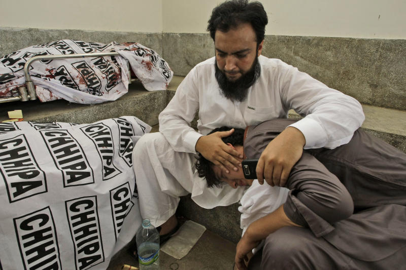 A Pakistani man comforts a family member next to the body of their relative who was killed in a bomb blast near a polling station on election day, at a hospital morgue in Karachi, Pakistan, Saturday, May 11, 2013. The blasts in the port city of Karachi targeted the political offices of the Awami National Party, one of three secular liberal parties that have been targeted by Taliban militants during the run-up to the election, said police officer Shabir Hussain. (AP Photo/Fareed Khan)