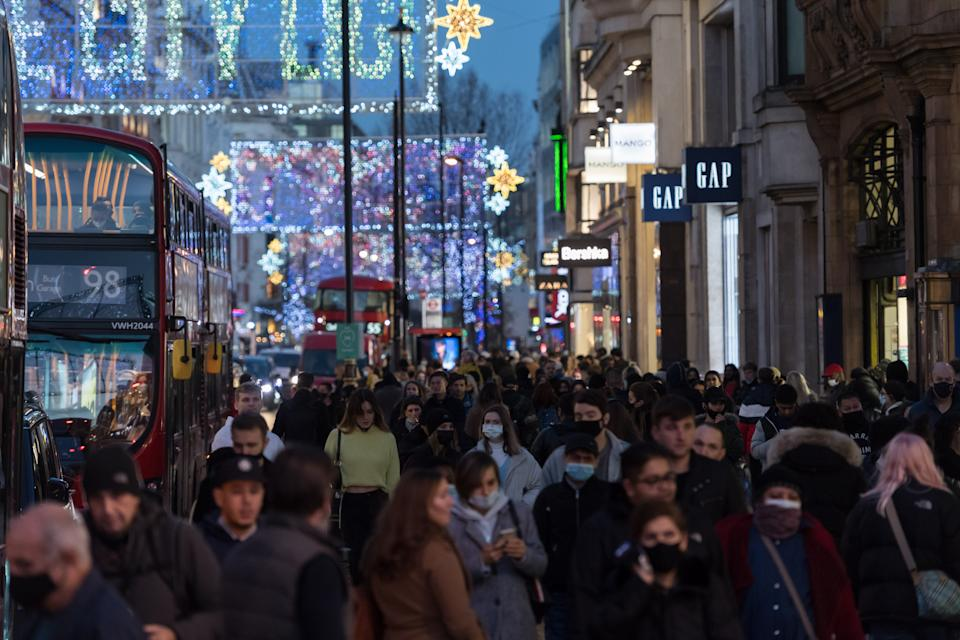 Crowds of shoppers and commuters walk along Oxford Street ahead of introduction of tougher coronavirus restrictions in the run up to Christmas, on 15 December, 2020 in London, England. From tomorrow, Greater London, as well as parts of Essex and Hertfordshire, will move into Tier 3 coronavirus restrictions resulting in closing of pubs, bars, restaurants, hotels and indoor entertainment venues such as theatres and cinemas, as the infection rates are well above the national average and continue to rise. (Photo by WIktor Szymanowicz/NurPhoto via Getty Images)