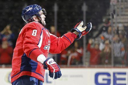 Dec 11, 2018; Washington, DC, USA; Washington Capitals left wing Alex Ovechkin (8) tosses a puck into the stands after the Capitals game against the Detroit Red Wings at Capital One Arena. The Capitals won 6-2. Mandatory Credit: Geoff Burke-USA TODAY Sports