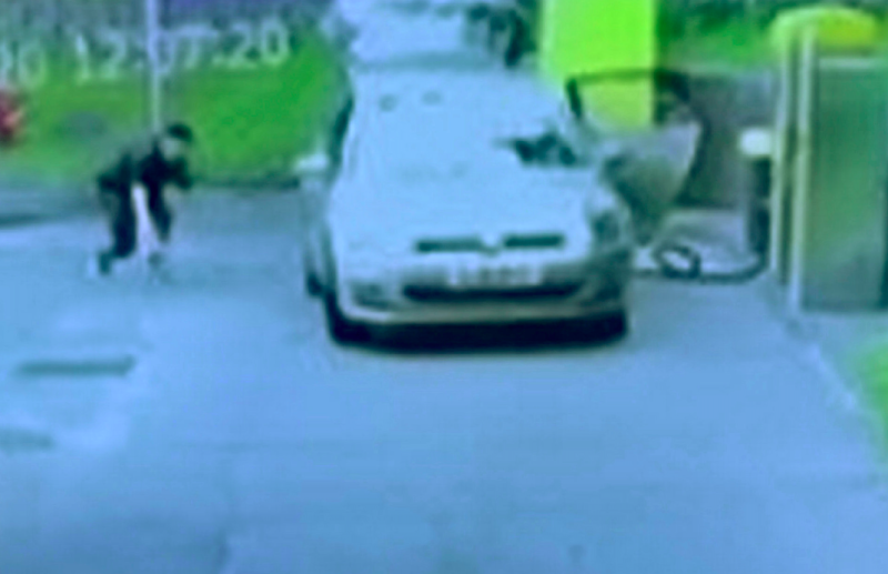 The thief sneaks up to the car while it was being vacuumed at a petrol station. (SWNS)