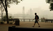 In this photo provided by Don Ryan, a pedestrian walks past the Willamette Bridge and downtown Portland, Ore., enveloped in heavy smoke from wildfires on Wednesday, Sept. 16, 2020. (Don Ryan via AP)