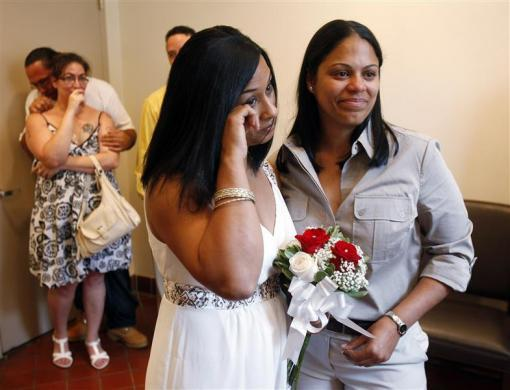 Same-sex couple Mishan Moore (L), 39, wipes a tear as her partner Jacqueline Rodriguez, 34, looks on during their wedding ceremony at Queens Borough Hall in New York July 24, 2011.