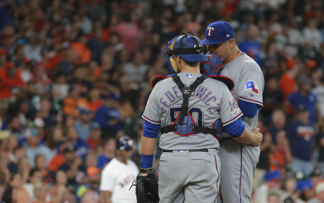 Texas Rangers pitcher Ariel Jurado, right, speaks with catcher Tim Federowicz during the third inning of a baseball game against the Houston Astros, Saturday, July 20, 2019, in Houston. (AP Photo/Richard Carson)