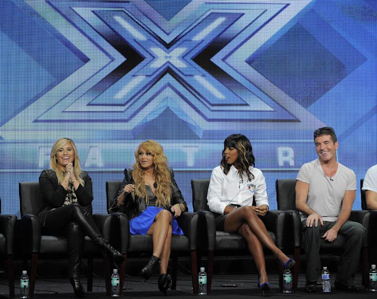 "Demi Lovato, from left, Paulina Rubio, Kelly Rowland and Simon Cowell, judges on the FOX series ""The X Factor,"" take part in a panel discussion on the show during the FOX 2013 Summer TCA press tour at the Beverly Hilton Hotel on Thursday, Aug. 1, 2013 in Beverly Hills, Calif. Cowell said the mostly female judges' panel for ""The X Factor"" reflects what he called the ""girls' world"" of today's music business. (Photo by Chris Pizzello/Invision/AP)"