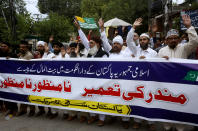 "Supporters of the religious group, Sunni Tehreek Pakistan, carry a banner in Urdu that reads, ""we disapprove the construction of Hindu temple in the Pakistani capital with government funds"", during a demonstration in Lahore, Pakistan, Sunday, July 12, 2020. Analysts and activists say minorities in Pakistan are increasingly vulnerable to Islamic extremists as Prime Minister Imran Khan vacillates between trying to forge a pluralistic nation and his conservative Islamic beliefs. (AP Photo/K.M. Chaudary)"