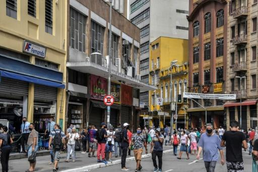 People walk down a commercial street in Rio de Janeiro after its reopening June 10, 2020