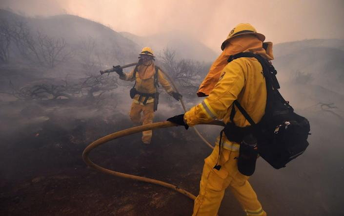 """<span class=""""caption"""">Firefighters have battled camp crud before, but COVID-19 brings new risks with the potential for heart and lung damage.</span> <span class=""""attribution""""><a class=""""link rapid-noclick-resp"""" href=""""https://www.gettyimages.com/detail/news-photo/riverside-county-firefighters-douse-embers-after-flames-news-photo/1014201966"""" rel=""""nofollow noopener"""" target=""""_blank"""" data-ylk=""""slk:Robyn Beck/AFP/Getty Images"""">Robyn Beck/AFP/Getty Images</a></span>"""