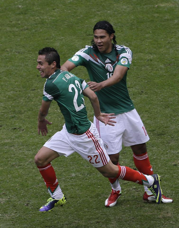 Mexico's Paul Aguilar, left, celebrates with teammate Carlos Pena after scoring against New Zealand at a 2014 World Cup playoff first round soccer match in Mexico City, Mexico, Wednesday, Nov. 13, 2013. (AP Photo/Dario Lopez-Mills)