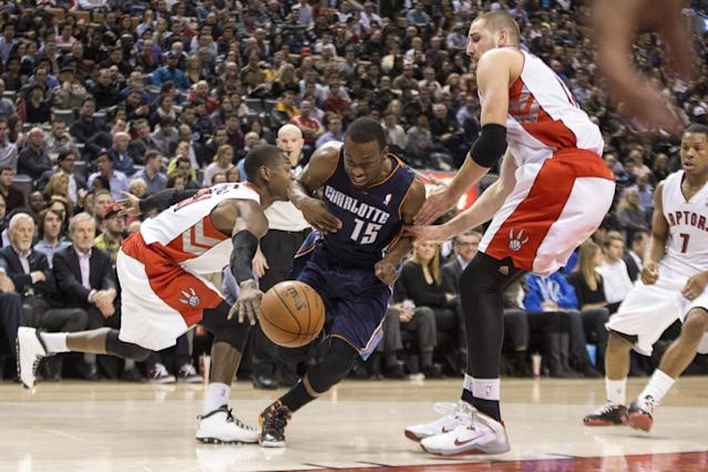 Charlotte Bobcats' Kemba Walker (drives between Toronto Raptors' Jonas Valanciunas, right, and Terrence Ross during the first half of an NBA basketball game in Toronto on Wednesday, Dec. 18, 2013. (AP Photo/The Canadian Press, Chris Young)