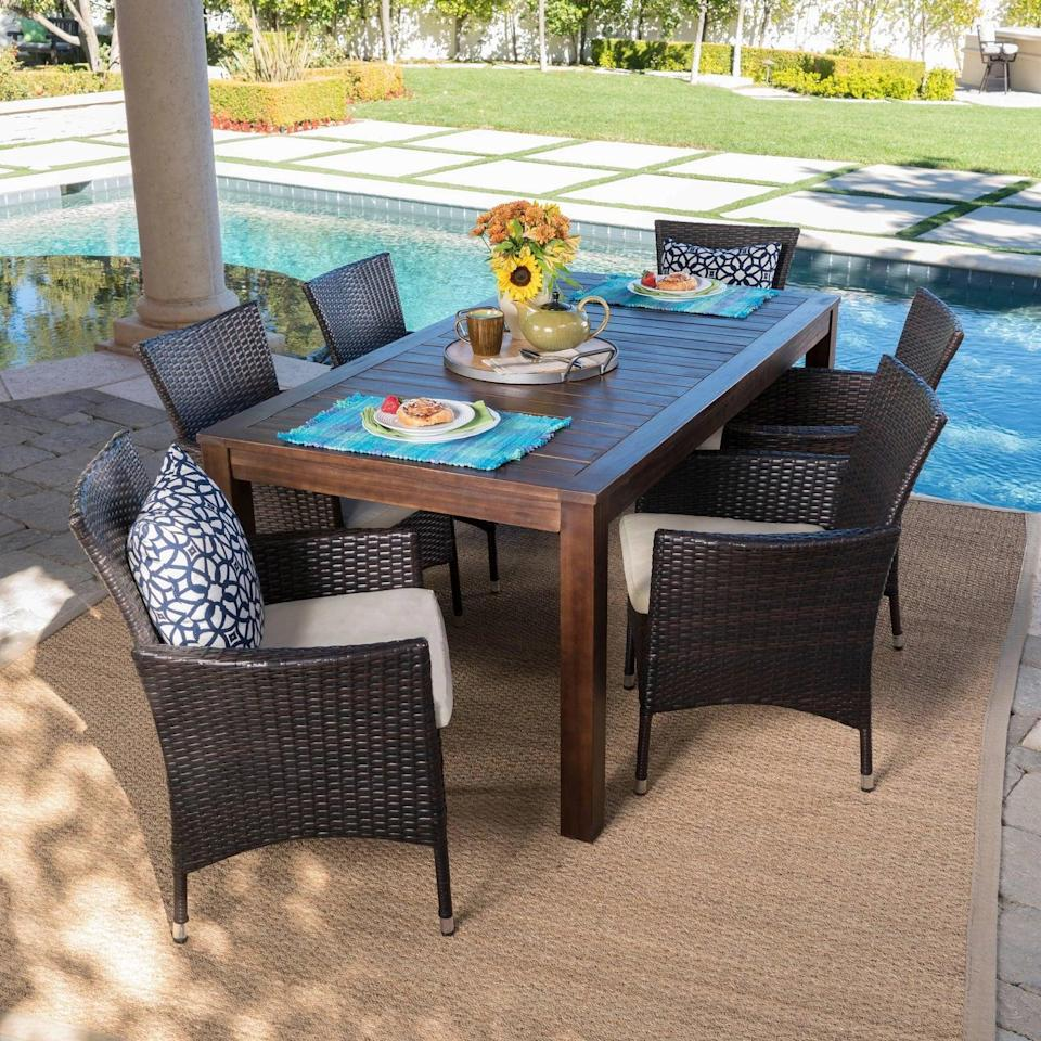 <p>You'll want to eat every family dinner on the <span>Lincoln Acacia Wood and Wicker Patio Dining Set</span> ($800).</p>