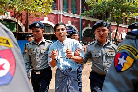 Detained Reuters journalist Kyaw Soe Oo is escorted by police after a court hearing in Yangon, Myanmar. REUTERS/Stringer