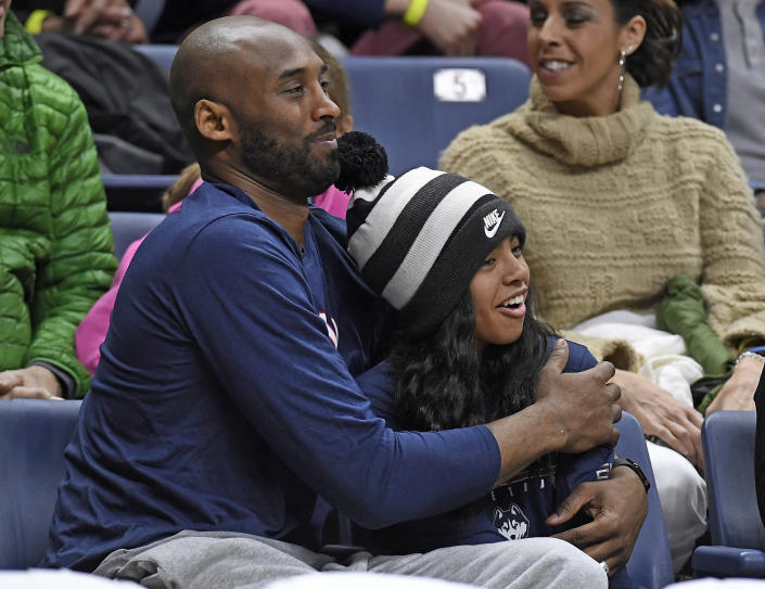 FILE - In this March 2, 2019, file photo, Kobe Bryant and his daughter Gianna watch the first half of an NCAA college basketball game between Connecticut and Houston in Storrs, Conn. Autopsy reports released Friday, May 15, 2020, show that the pilot who flew Bryant did not have drugs or alcohol in his system when the helicopter crashed in Southern California in January, killing all nine aboard. The causes of death for Bryant, his 13-year-old daughter Gianna, pilot Ara Zobayan and the others have been ruled blunt force trauma. Federal authorities are still investigating the Jan. 26 incident where the chopper crashed into the Calabasas hillsides. (AP Photo/Jessica Hill, File)
