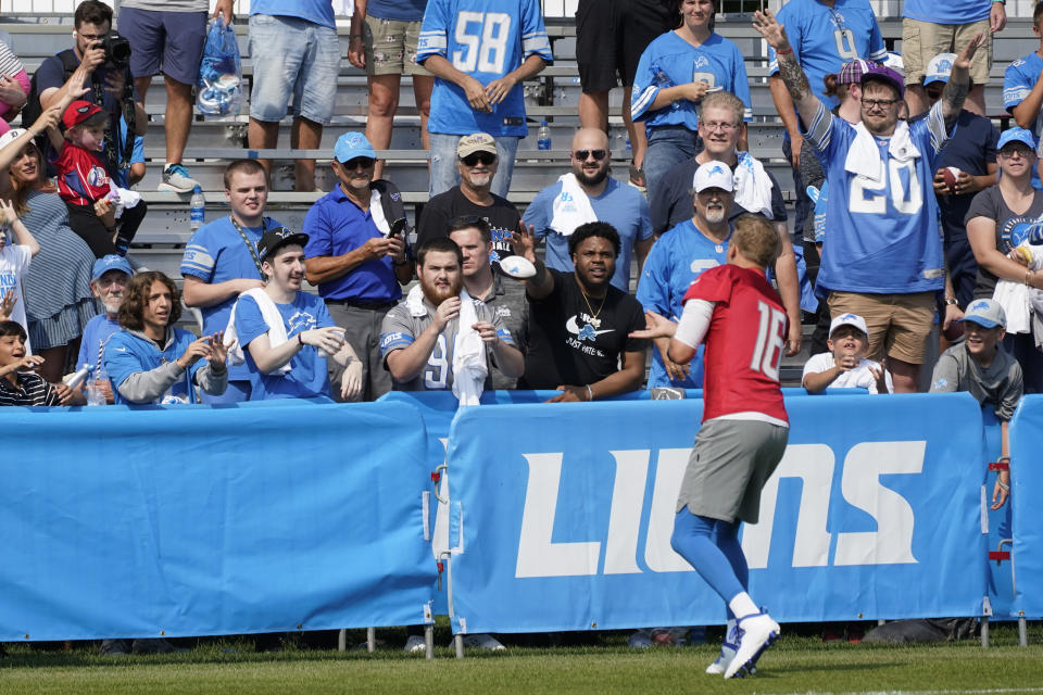 Detroit Lions quarterback Jared Goff (16) throws a football to fans after an NFL football training camp practice in Allen Park, Mich., Saturday, July 31, 2021. (AP Photo/Paul Sancya)
