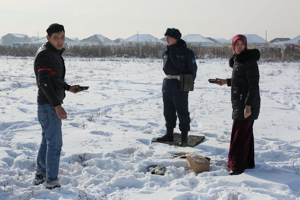 Local residents offer food to a soldier cordoning off the site of a passenger plane crash outside Almaty on December 27, 2019. - At least 15 people died on December 27, 2019 and dozens were injured when a passenger plane carrying 100 people crashed shortly after takeoff from Kazakhstan's largest city and slammed into a house, state media reported. (Photo by Ruslan PRYANIKOV / AFP) (Photo by RUSLAN PRYANIKOV/AFP via Getty Images)