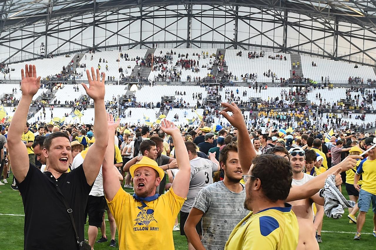 Clermont's supporters invade the pitch after the French Top 14 rugby union semi-final match between Racing 92 and Clermont-Ferrand on May 27, 2017 at the Velodrome Stadium in Marseille, southern France. Clermont defeated Racing 92, 37-31. (AFP Photo/BORIS HORVAT)