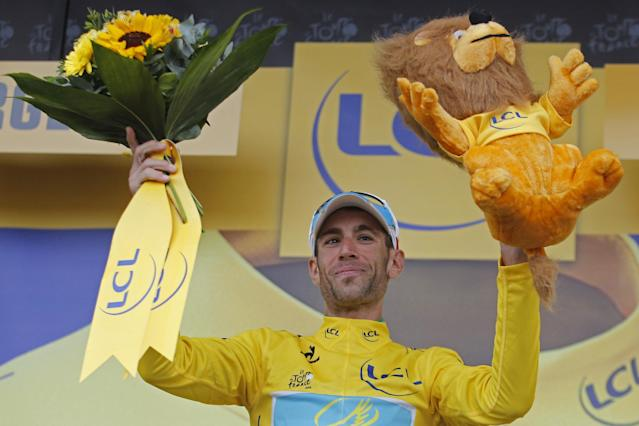 Italy's Vincenzo Nibali, wearing the overall leader's yellow jersey, celebrates on the podium of the nineteenth stage of the Tour de France cycling race over 208.5 kilometers (129.6 miles) with start in Maubourguet and finish in Bergerac, France, Friday, July 25, 2014. (AP Photo/Christophe Ena)