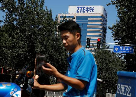 A delivery man uses a phone near a building of China's ZTE Corp in Beijing, China, August 29, 2018.  REUTERS/Thomas Peter