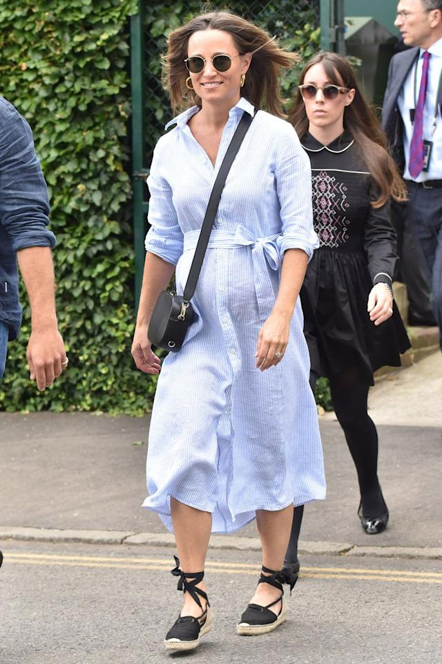 "<p>In a light blue striped <a rel=""nofollow"" href=""https://www.ralphlauren.com/women-clothing-dresses/striped-linen-shirtdress/428176.html"">Ralph Lauren shirtdress</a>, black lace-up espadrilles, a black leather crossbody bag, sunglasses, and gold hoop earrings at Wimbledon. </p>"